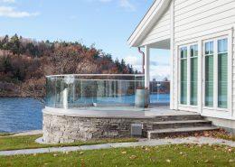 Et rekkverk med buet glass, innfestet i diskre profiler, gir huset flotte og spennende kvaliteter. Foto: Peder Gjerso